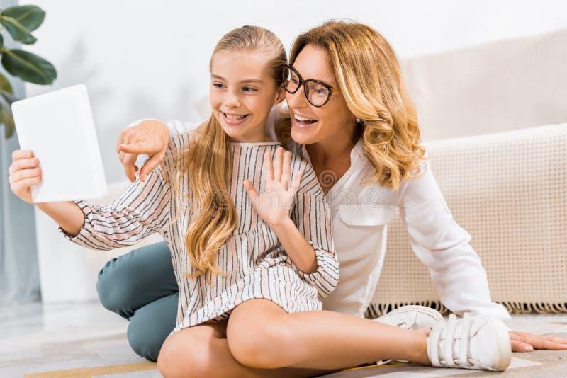selectieve nadruk van gelukkige grootmoeder en kleindochter die met de hand en videogesprek met digitale tablet golven hebben stock foto