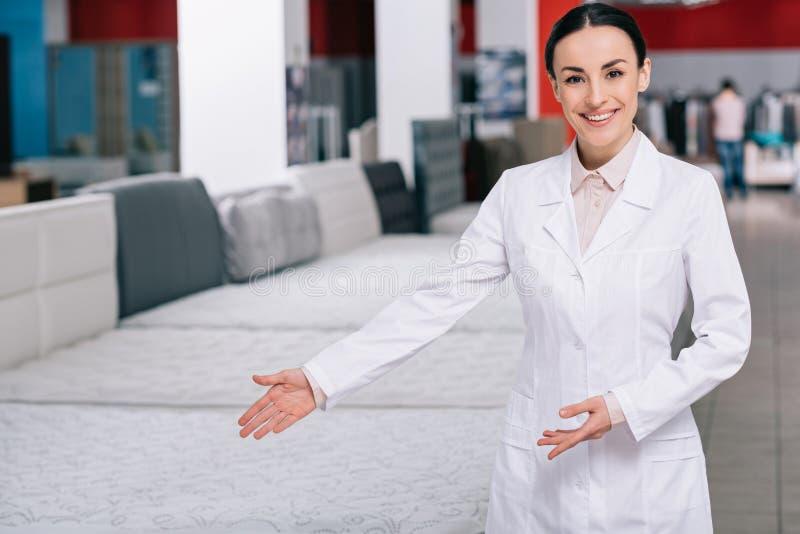 selectieve nadruk van glimlachende winkelmedewerker die in witte laag op orthopedische matrassen richten stock fotografie