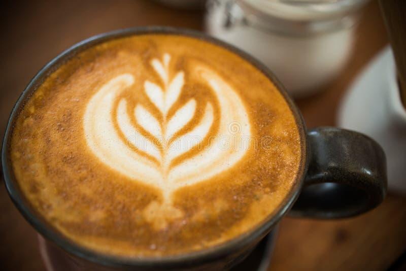 Selectieve nadruk van het schuimpatroon van de lattekunst bovenop de kop van de cappuccinokoffie voor koffiepauzetijd stock foto