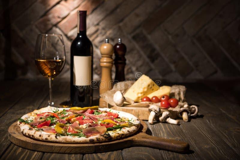 selectieve nadruk van Italiaanse pizza, kruiden, kaas, kersentomaten en fles wijn op houten oppervlakte stock afbeelding