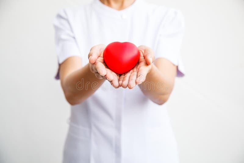 Selectieve nadruk van rood die hart door vrouwelijke verpleegster ` s beide hand wordt gehouden, die gevend al inspanning om hoog stock afbeelding