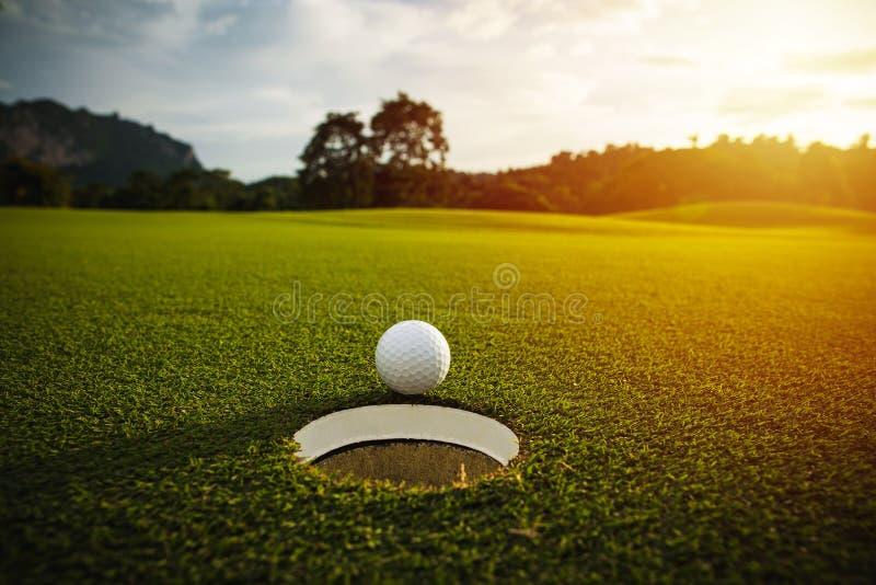 Selectieve nadruk witte golfbal dichtbij gat op groen gras goed F royalty-vrije stock fotografie