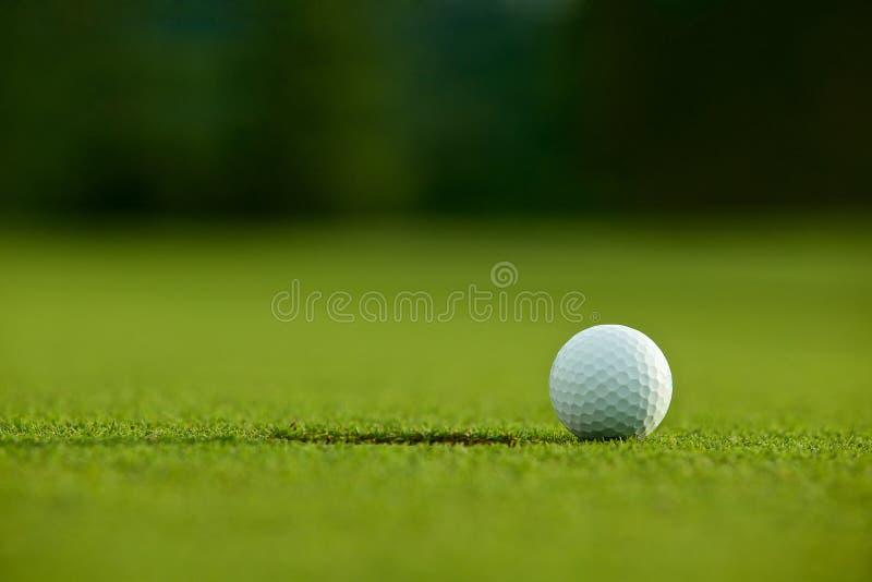 Selectieve nadruk witte golfbal dichtbij gat op groen gras goed F stock afbeeldingen