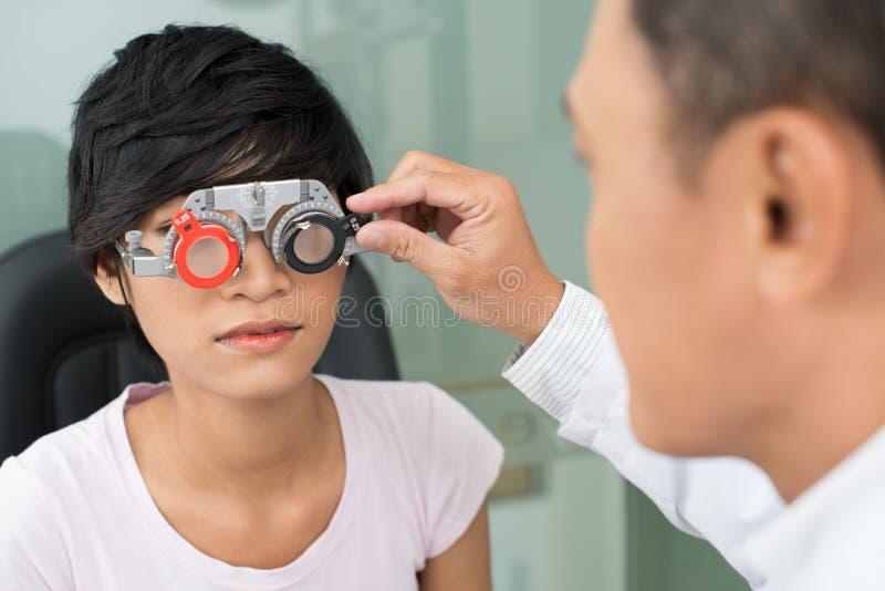 Selecting eyeware. Mature optician selecting eyeglasses to female patient stock photography