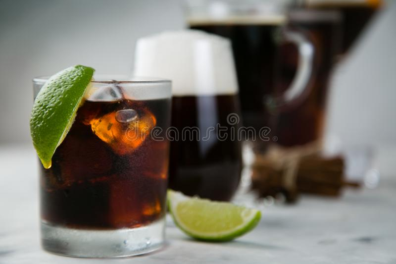 Selection of black cocktails in different glasses, marble background stock photography