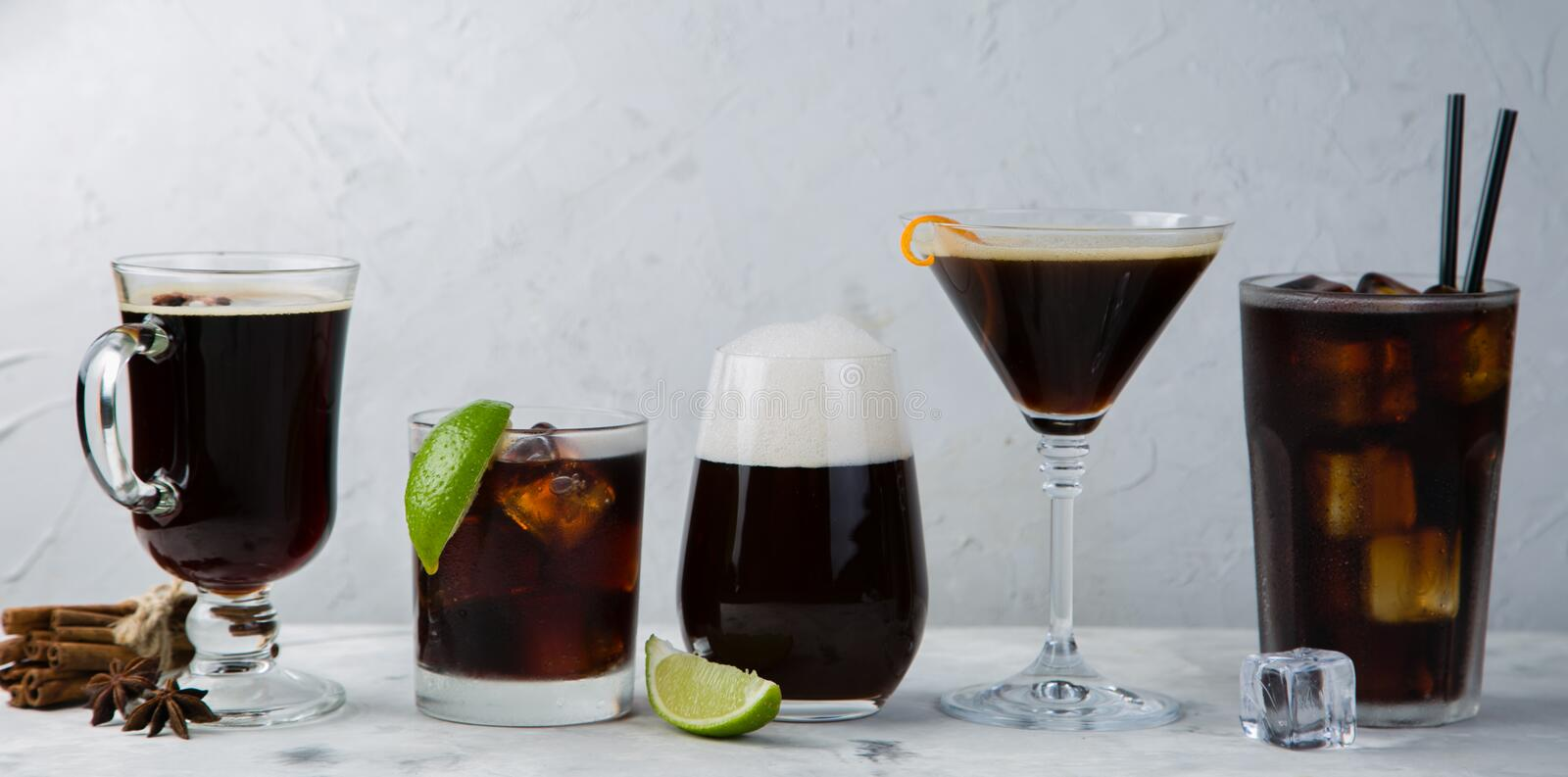 Selection of black cocktails in different glasses, marble background stock image
