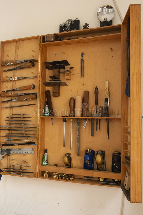 Selection of carpentry tools in cabinet. Hanging on the wall, with small hand planes and woodmaking tools stock image