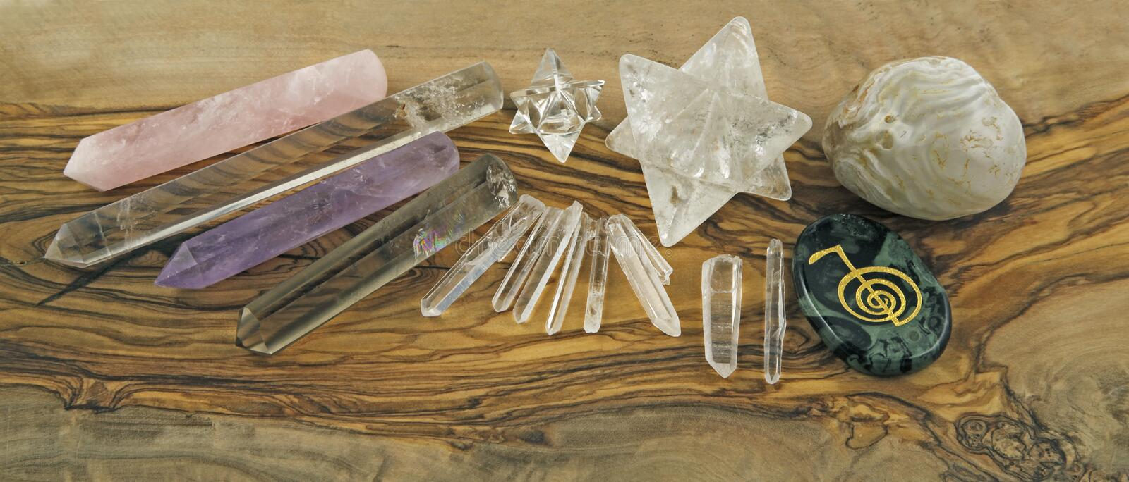 Selection of Crystal healer's tools. Including small and large Merkabah, four crystals wands, agate, Reiki Symbol stone and terminated quartz on olive wood stock image