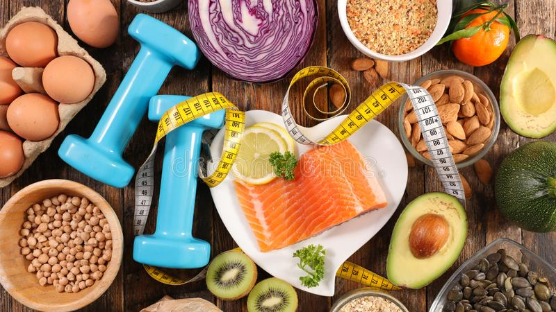 Selection of diet food. Salmon with dumbbell and healthy food stock photo