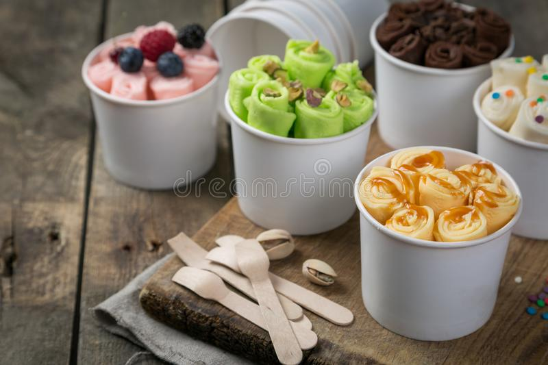 Selection of different rolled ice creams in cone cups royalty free stock photography