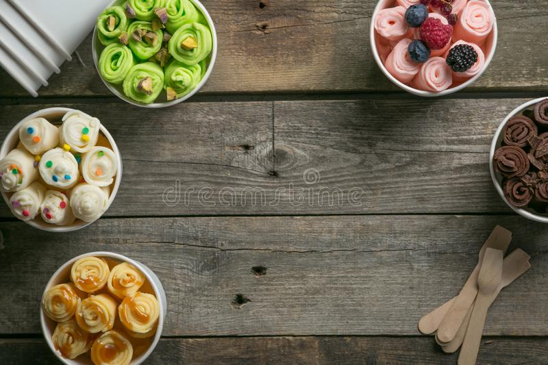 Selection of different rolled ice creams in cone cups stock image
