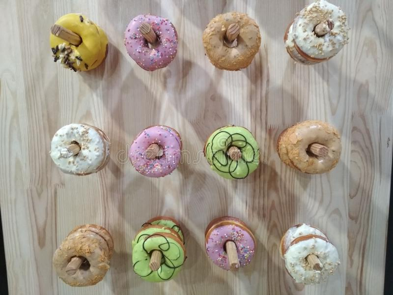 Selection of donuts with colored glaze on a wooden background. stock image