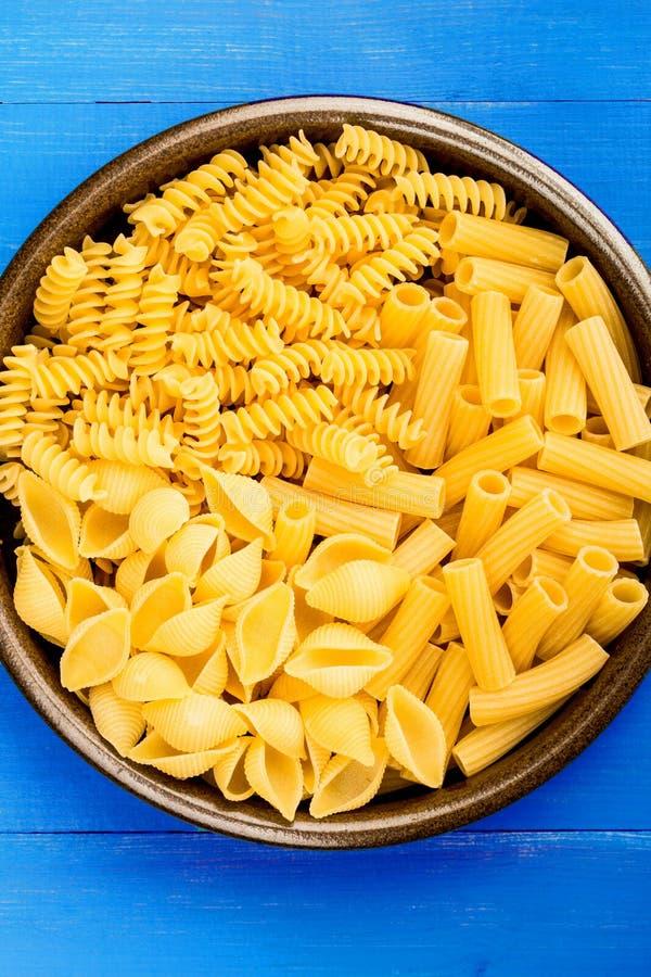 Selection of Dried Uncooked Italian Style Pasta Conchiglioni Rigatoni and Fusilli royalty free stock image