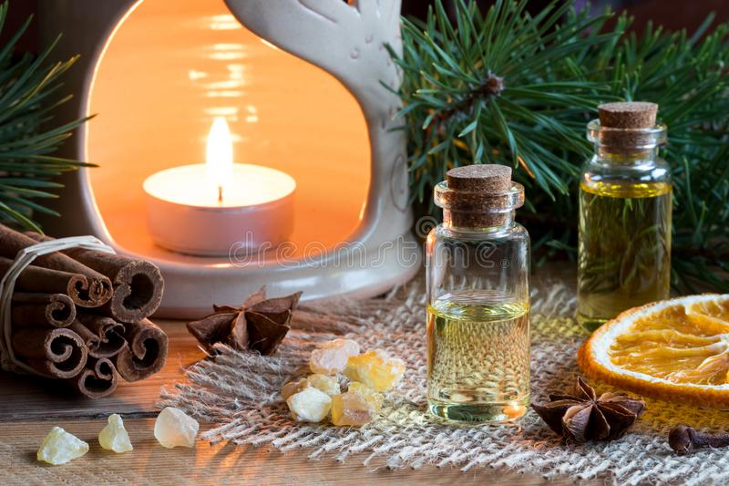 Selection of essential oils with star anise, cinnamon, frankincense, clove, dried orange royalty free stock photos