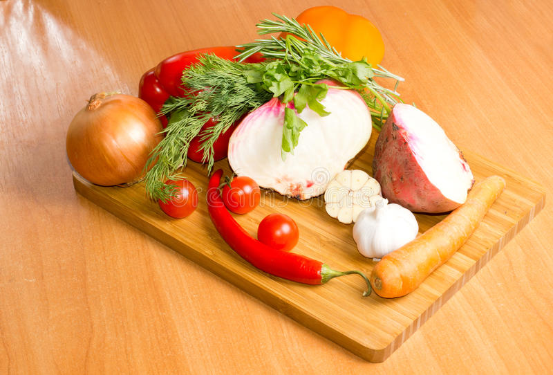 Fresh vegetables on a chopping board. Selection of farm fresh vegetables and sprigs of herbs on a chopping board in the kitchen ready to be turned into a royalty free stock images