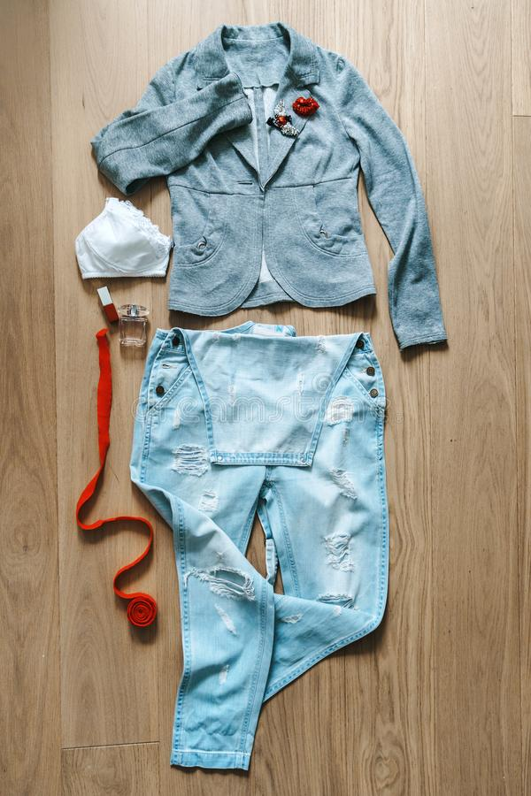 Selection of a female image from a denim overall, gray jacket, white bra and red accessories, brooch, toilet water, and a belt. stock images