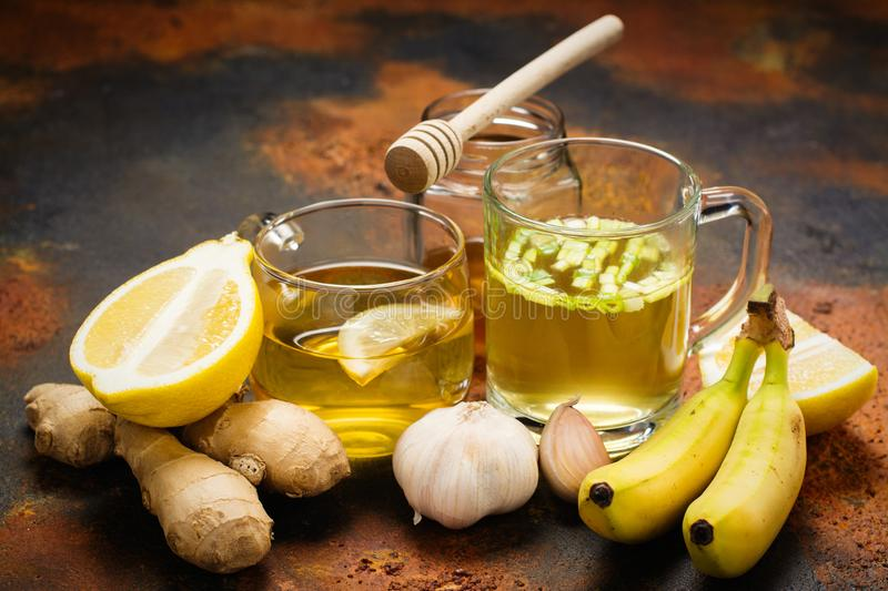 Selection of food against flu. Natural product for excellent immunity - herbal tea, lemon, ginger, honey, bananas and broth soup. Space for text stock images