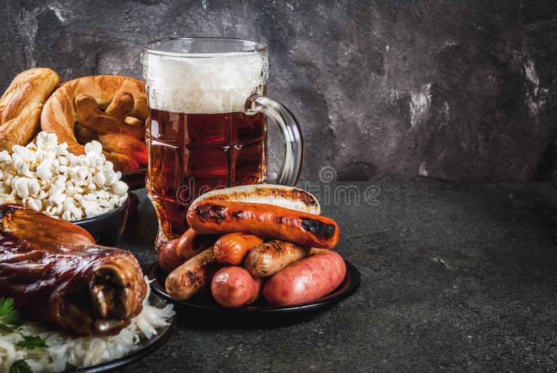 Selection food for Oktoberfest. Selection of traditional German food Oktoberfest. Beer, baked pork shank, popcorn, assortment of different sausages, homemade royalty free stock photography