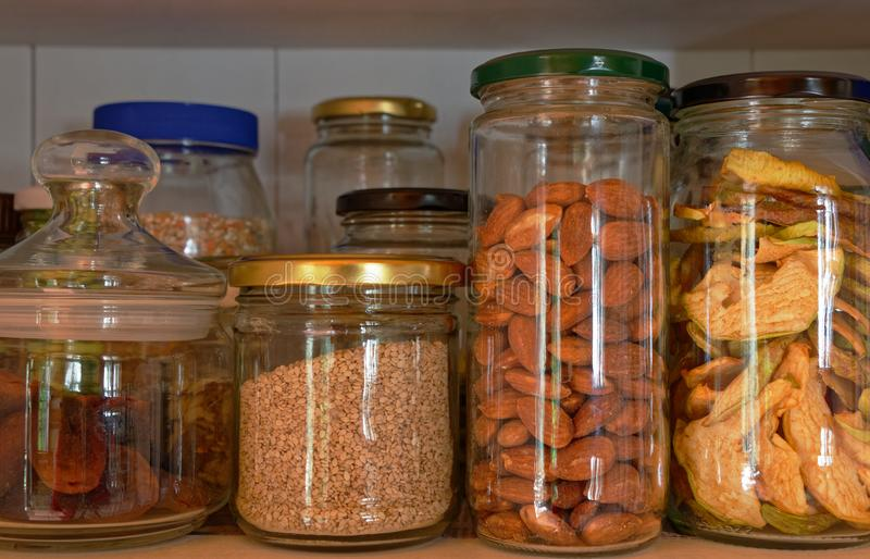 A selection of glass jars with nuts and grains stored in them. Glass storage jars lined up in a cupboard filled with nuts, dried apples and grains royalty free stock images