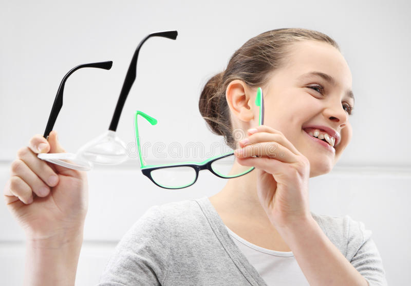 Selection of glasses, a little girl with an ophthalmologist stock photo