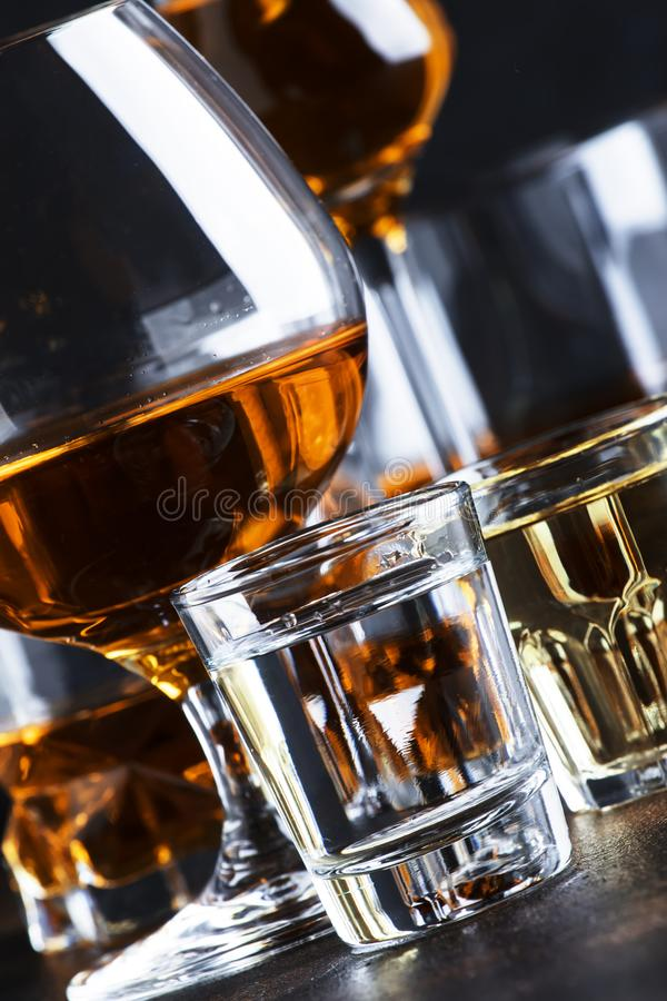Selection of hard alcoholic drinks in big glasses and small shot glass in assortent: vodka, rum, cognac, tequila, brandy and stock images
