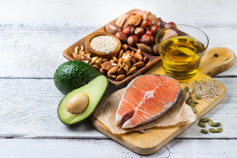 Selection of healthy fat sources food, life concept. Selection of healthy fat sources food, salmon fish avocado olive oil pumpkin seeds nuts sesame on a white stock image