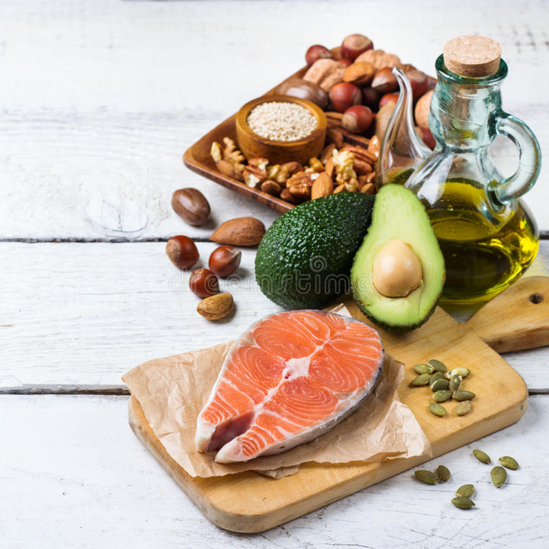Selection of healthy fat sources food, life concept. Selection of healthy fat sources food, salmon fish avocado olive oil pumpkin seeds nuts sesame on a white royalty free stock image