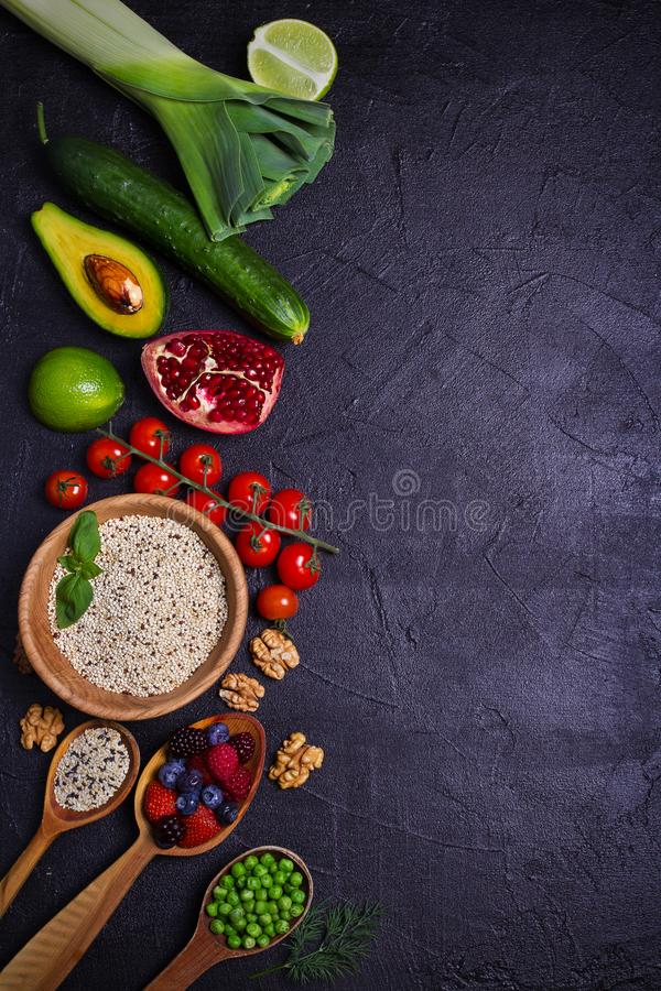 Selection of healthy food. Food background: quinoa, pomegranate, lime, green peas, berries, avocado, nuts and olive oil. Slate banner background. overhead royalty free stock photos