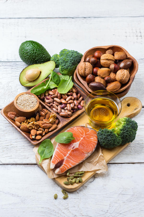Selection of healthy food for heart, life concept. Selection of healthy food for heart, salmon fish avocado olive oil pumpkin seeds nuts broccoli green spinach stock photography