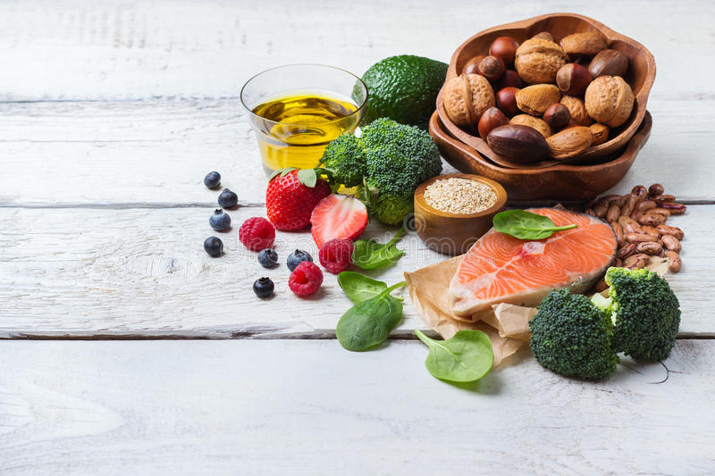 Selection of healthy food for heart, life concept. Selection of healthy food for heart, salmon fish avocado olive oil pumpkin seeds nuts broccoli green spinach royalty free stock photography