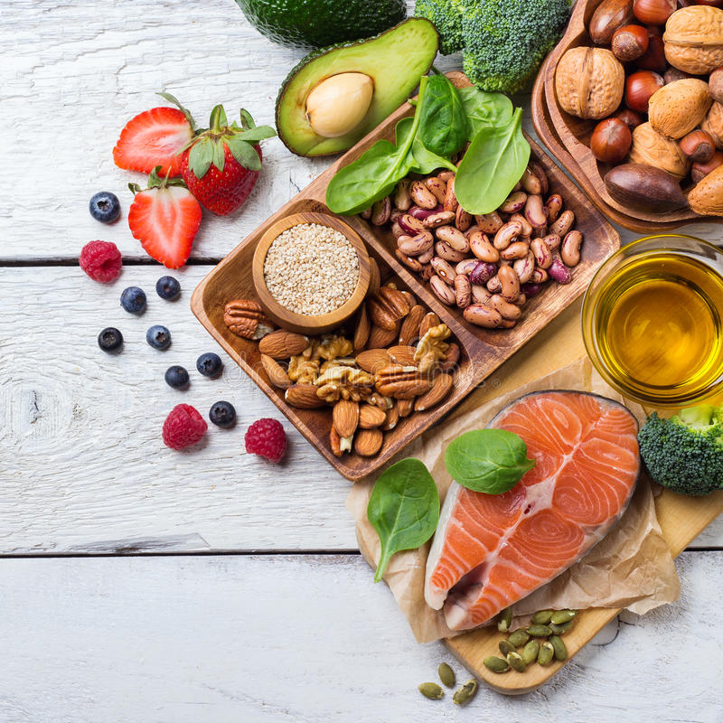 Selection of healthy food for heart, life concept. Selection of healthy food for heart, salmon fish avocado olive oil pumpkin seeds nuts broccoli green spinach stock image