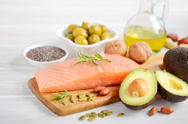 Selection of healthy unsaturated fats, omega 3 - fish, avocado, olives, nuts and seeds. royalty free stock photography