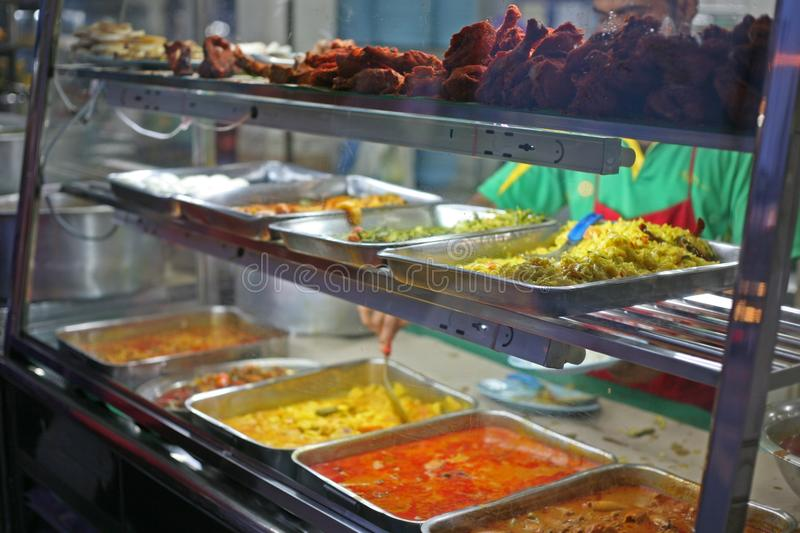A selection of Indian curries and tandoori chicken. Spooning fresh curry in a Malacca Indian restaurant, Malaysia royalty free stock photo