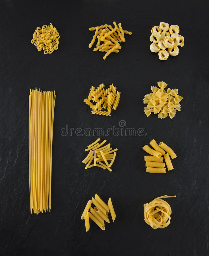 Selection of pasta uncooked, isolated on black slate background royalty free stock photo