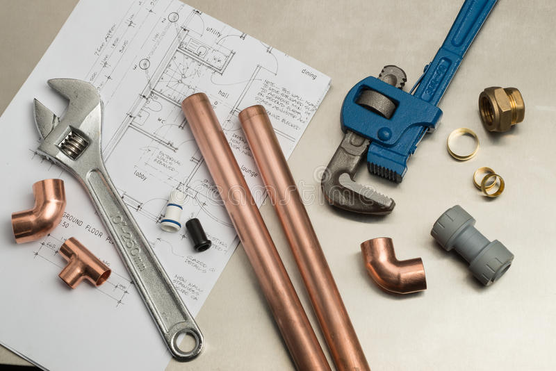 Selection of Plumbers Tools and Plumbing Materials. Various plumbers tools and plumbing materials including copper pipe, elbow joint, wrench and spanner. shot on royalty free stock photography