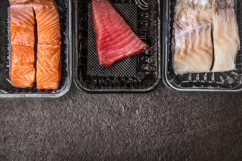 Selection of raw colorful fish fillets : salmon, tuna and codfish in plastic boxes on dark rustic background, top view, border, pl stock photography