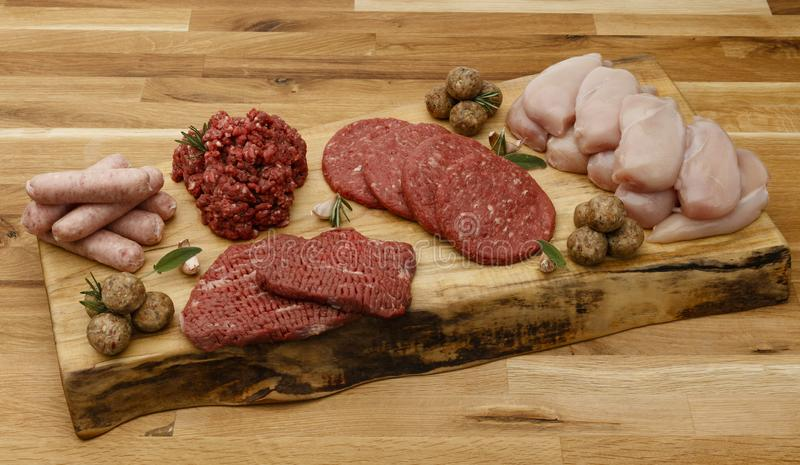 Selection of raw meat full of protien. Arranged on a wooden chopping board, with herbs and garlic royalty free stock photos