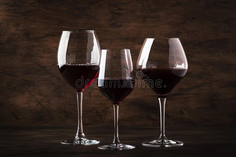 Selection of red wine on wine tasting. Dry, semi-dry, sweet red wines in special wine glasses on old wooden table background. Copy royalty free stock photography