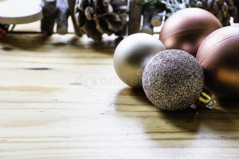 A selection of rose gold Christmas decoration baubles on a wooden table. With a pine cone chain in the background royalty free stock photo