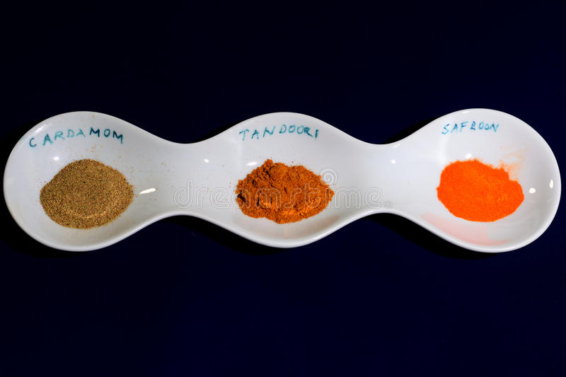 Selection of spices, Cardamom, Tandoori and Saffron. Three spices in a white dish royalty free stock photos