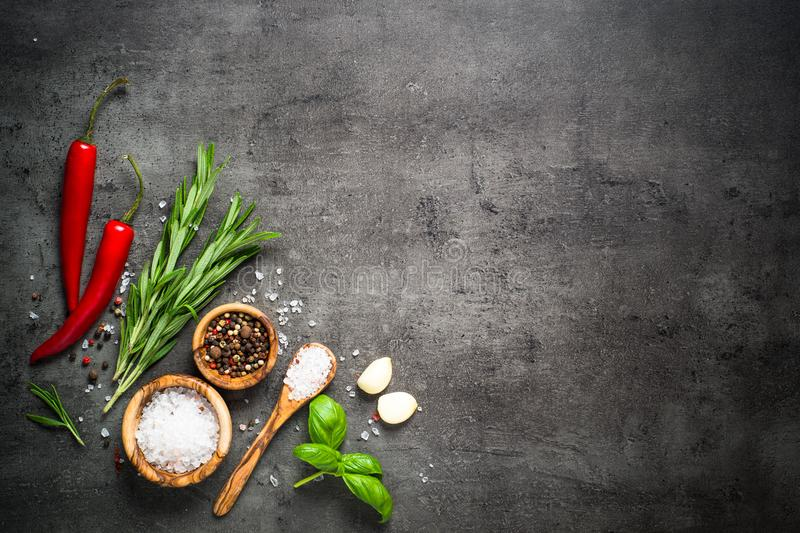 Selection of spices herbs and greens on black top view. royalty free stock photos