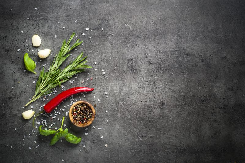 Selection of spices herbs and greens on black top view. royalty free stock photo