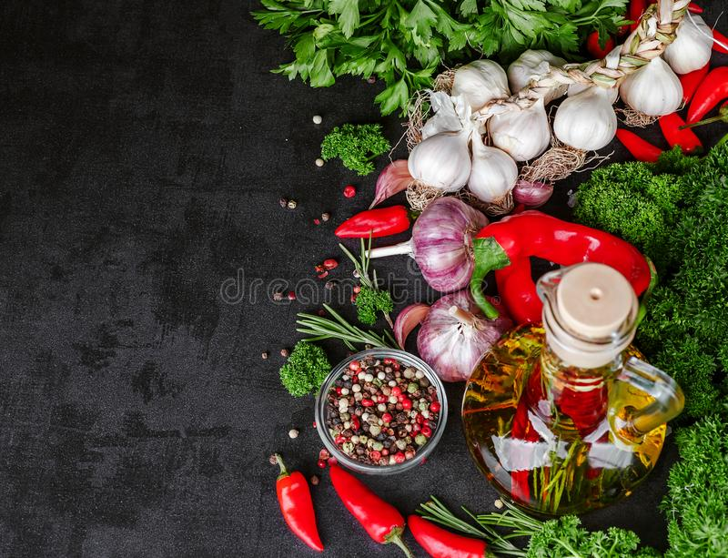 Selection of spices herbs and greens. Ingredients for cooking. Food background on black slate table stock photo