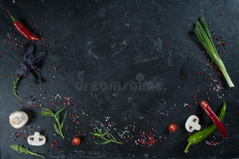 Selection of spices herbs and greens. Ingredients for cooking. Food background on black slate table. Top view copy space royalty free stock photography
