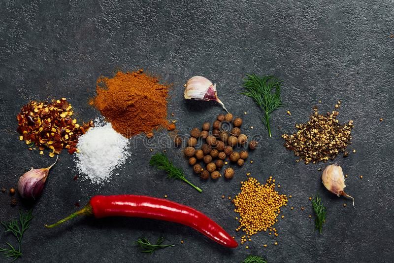 Selection of spices herbs and greens. Ingredients for cooking. Food background on black slate table. royalty free stock images