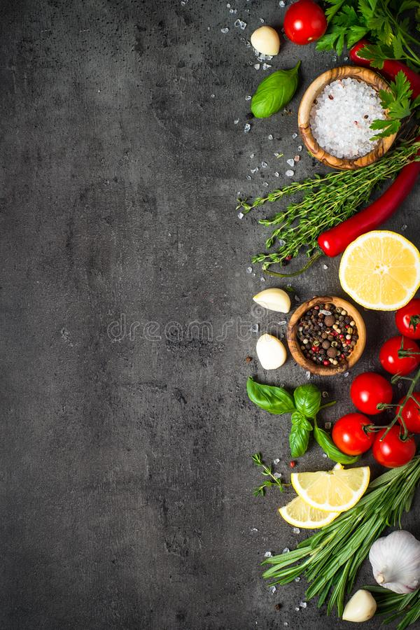 Selection of spices herbs and vegetables on black top view. royalty free stock photo