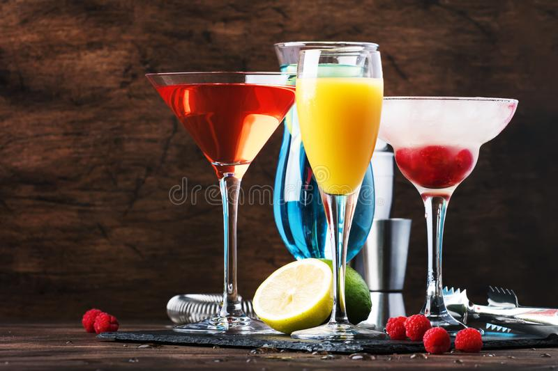 Selection of summer cocktails. Cold refreshing alcoholic beverages and drinks: mimosa, cosmopolitan, raspberry margarita and blue. Hawaii on wooden bar counter stock photos