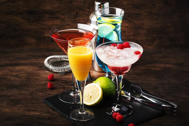 Selection of summer cocktails. Cold refreshing alcoholic beverages and drinks: mimosa, cosmopolitan, raspberry margarita and blue. Hawaii on wooden bar counter stock image