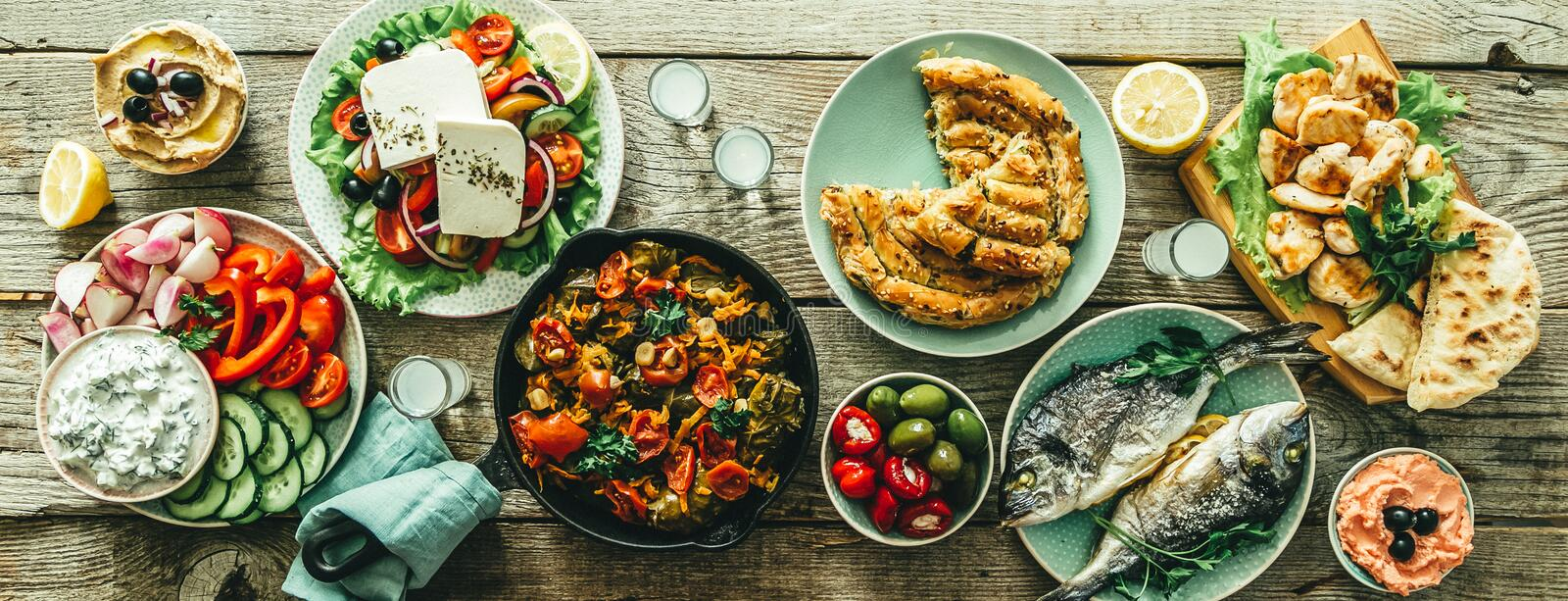 Selection of traditional greek food - salad, meze, pie, fish, tzatziki, dolma on wood background. Top view stock photography