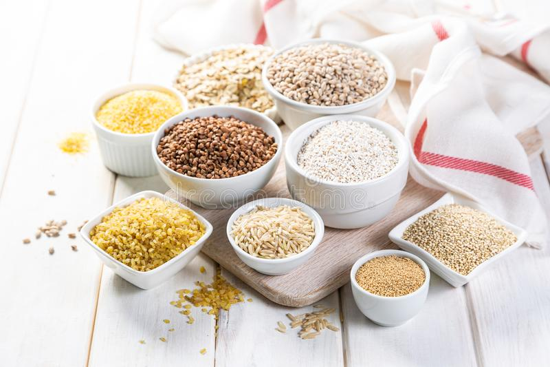 Selection of whole grains in white bowls - rice, oats, buckwheat, bulgur, porridge, barley, quinoa, amaranth, stock photos